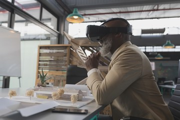 Male executive using virtual reality headset at table