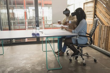 Male and female executives using virtual reality headset