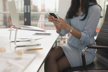 Female executive using mobile phone at table