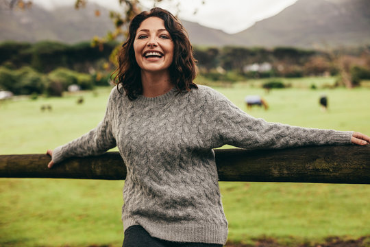 Cheerful woman leaning to a fence in countryside