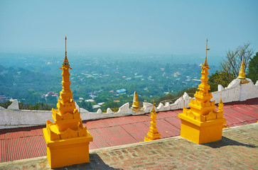 The golden stupas of U Min Thonze Caves with a view on foggy green plain of Sagaing, Myanmar.