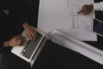 Business executives using laptop and pointing towards blue print