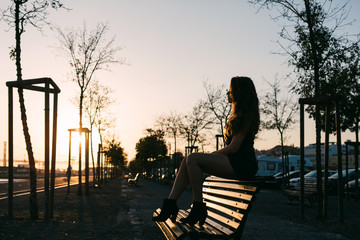 Young woman in casual wear sitting on bench