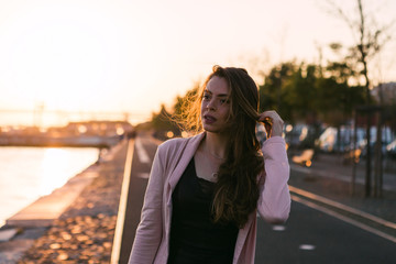 Young woman in casual wear walking on embankment