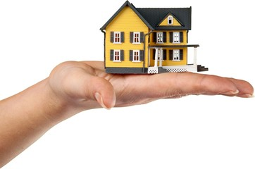 hand with a miniature house model