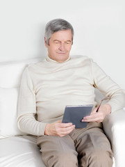 Handsome old man in casual wear is using a digital tablet