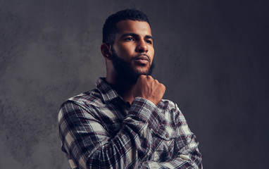 Portrait of a pensive African-American guy with a beard wearing a checkered shirt