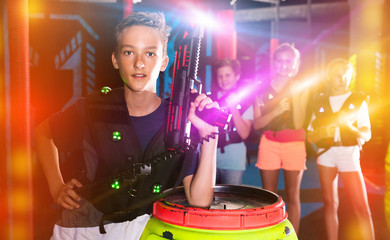 Boy with laser pistol in lasertag room