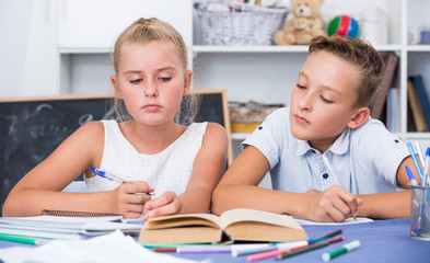 Boy with girl are writing in notebook their homework