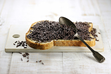 Dutch white bread with hagelslag (chocolate sprinkles) topping on ceramic board