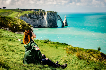 photo of beautiful young woman relaxing and looking at the splendid Etretat.