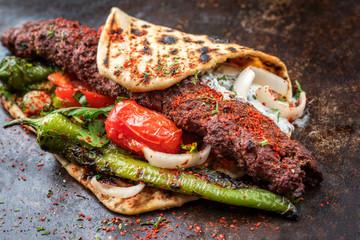 Traditioneller Adana Kebap Grillspieß mit Tomaten und  with tomato and Jogurt als  closeup auf einem Fladenbrot