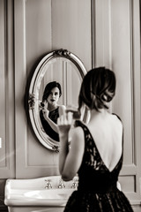 portrait of beautiful young woman with comb looking at herself in the wonderful mirror . Image in black and white color style