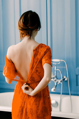 photo of beautiful young woman standing near bath and taking her dress off