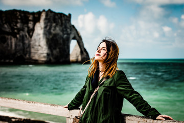 portrait of beautiful young woman standing on the wonderful cliffs and sea background