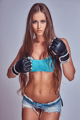Beautiful boxing girl wearing fighting gloves, posing for a camera, isolated on a gray background.