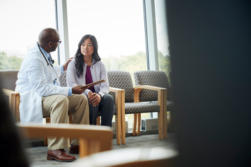 Doctor talking to woman in medical office