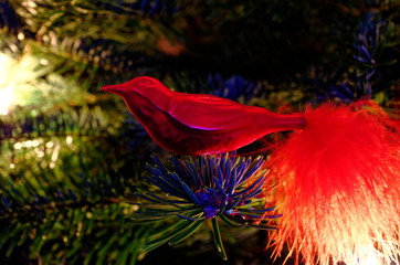 Christmas bauble bird on a Christmas tree and glowing lights