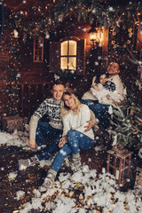Christmas portrait of two couples. Gladly smile at each other, hug and sit at a fabulous Christmas home with decorative snow and tree. Studio New Year's photo.