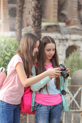 Two tourist teen girls have fun and make photo with camera