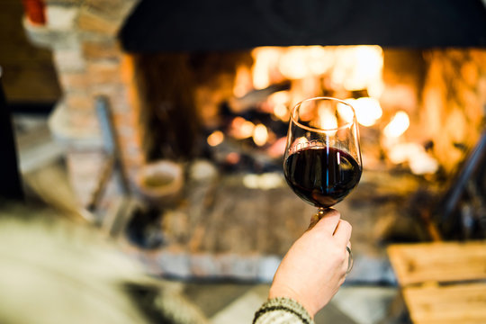Holding a glass of wine by the fireplace