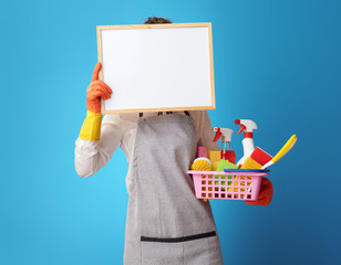 cleaning woman with a basket with detergents and brushes holding