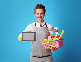 housemaid with a basket with detergents and brushes showing tabl