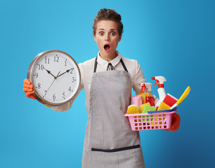 scrubwoman with a basket with cleansers, brushes and clock