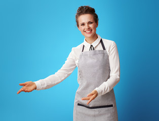 happy young housemaid in apron on blue welcoming