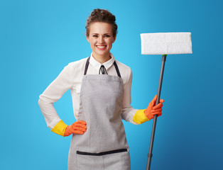 happy young cleaning lady in apron with mop on blue