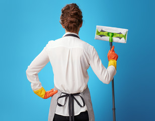 Seen from behind young cleaning lady in apron on blue with mop