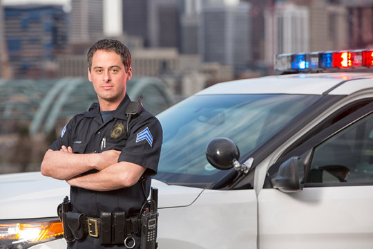 Police sergeant leaning agains car
