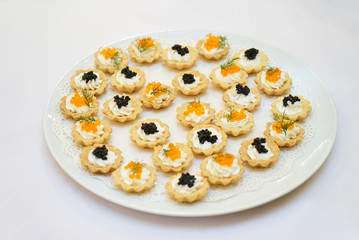 Tartlets with black and red caviar on a white plate
