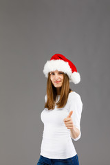 Beautiful woman in Santa Claus clothes showing OK sign