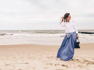 Woman holding camera at beach