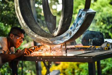 Man welding metal sculpture