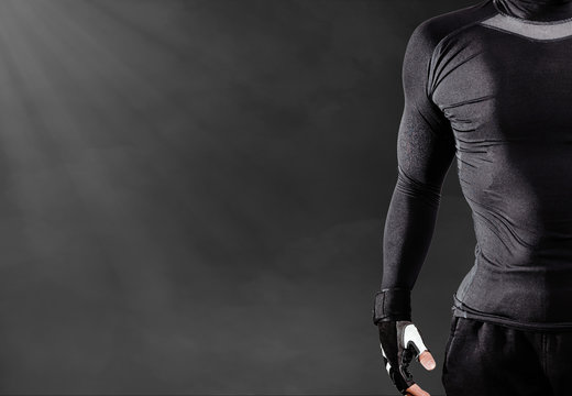Half of a man dressed in a black sports sweatshirt. Muscled, athletic man stands on a black, misty background. Concept of exercise at the gym, training, making muscles.