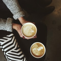 Overhead view of woman's hand holding coffee cup