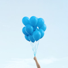 Man's hand holding bunch of blue balloons