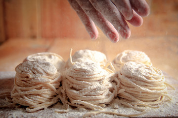 Close up of man's hand dusting flour on homemade noodles