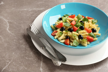 Plate with delicious pasta primavera on grey background