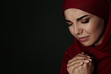 Portrait of sad Muslim woman in hijab  praying on dark background. Space for text