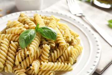Plate with delicious basil pesto pasta on table, closeup