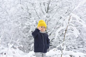Hello, winter! Handsome boy in black warm jacket and yellow knitted cap. Kid in snow waving hand hello. Friendly boy smiles in the winter forest. Happy childhood. Positive children. Winter walk