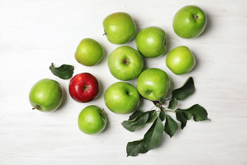 Red apple among green ones on wooden background, top view. Be different
