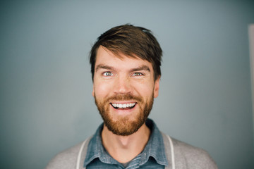 Close up of smiling man against blue background