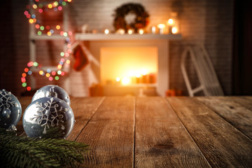 wooden table with attributes of Christmas in the glow of the fireplace