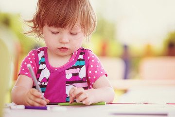 little girl drawing a colorful pictures