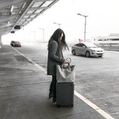 Woman standing with her luggage outside the airport