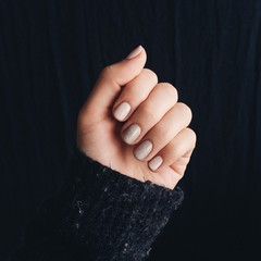 Close up of woman's hand with nail polish against black background